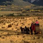 Stagecoach across grassy meadow